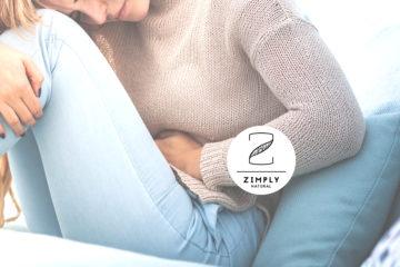 Junge Frau auf dem Sofa sitzend die sich den Bauch hält