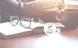 Frau die am Schreibtisch sitzt auf dem Buch, Brille und Tasse liegen