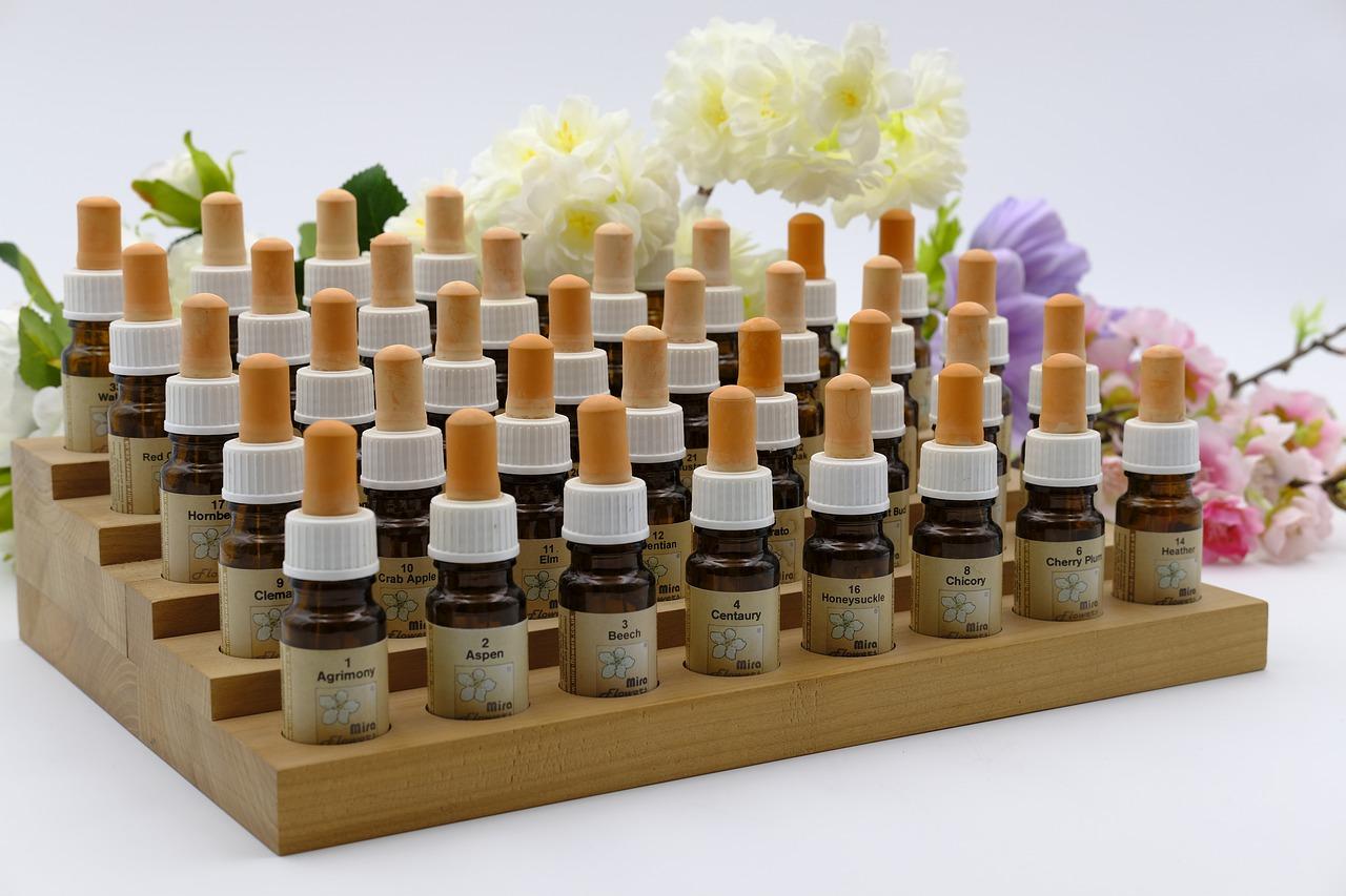 die 38 Bachblütenessenzen auf einem Podest für Essenzflaschen, nacheinander aufgereiht und beschriftet, Blumen liegen im Hintergrund