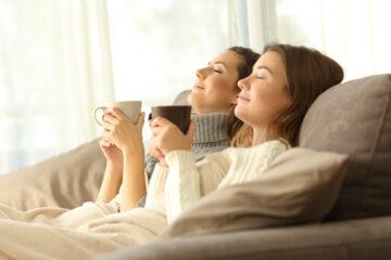 Zwei Frauen die entspannt auf dem Sofa Tee trinken