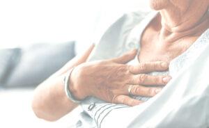 Frau hält Hand an Brustbein wegen Sodbrennen